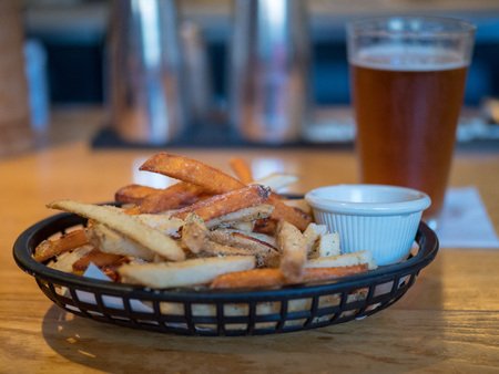 Close up of french fries at a bar on a wooden bar counter