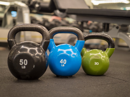 Row of kettlebells in a modern gym. 50, 40, and 30 lbs