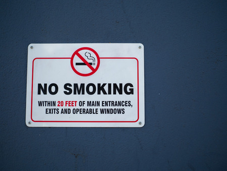 No smoking within 20 feet of main entrances sign hanging on a wall outdoors 版權商用圖片