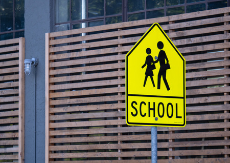 School zone warning sign posted on street near school grounds