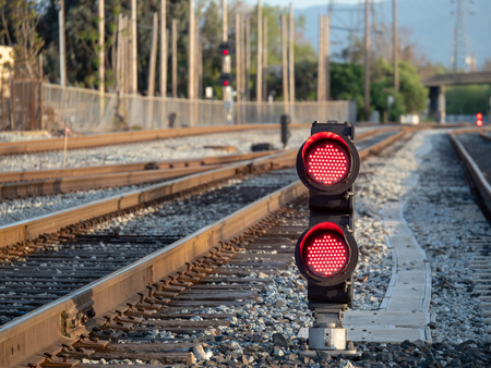 A railroad color position light sits on ground level flashing red stop lights Banco de Imagens