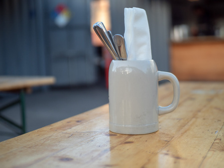 Napkin and utensil cup sitting on table in outdoor restaurant Banque d'images - 99977845