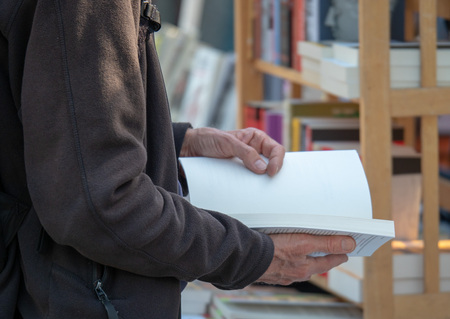 Man reading paperback book at a book store while standing Banco de Imagens