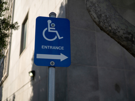 Handicap entrance sign pointing to the right in a sunny outdoor area Stock Photo