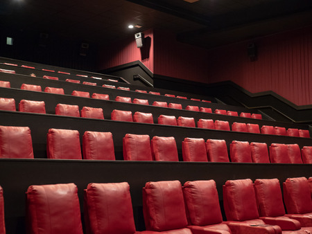 Rows of luxury red movie theater seats in an empty movie theater Stock Photo