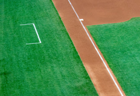 Empty third base and coach box of a baseball diamond with natural grass
