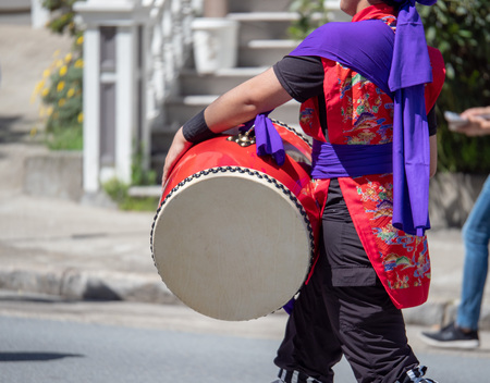 Man in kimono playing a Japanese wadaiko percussion drum as part of a band Stock Photo