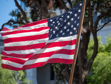 United States flag flowing in the wind by a flagbearer outdoors