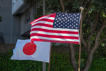 Japanese and American flags flowing in the wind outdoors in the shade
