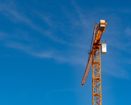 Crane high in view amidst sunny day outside in a sunny area Stock Photo