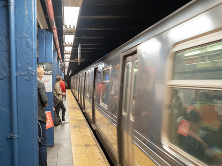 NEW YORK, NY – MAY 18, 2018: Metropolitan Transportation Authority (MTA) subway train whizzing by waiting passengers on 81st street station platform 新聞圖片