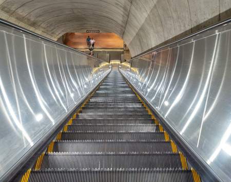 Escalator descending into dark tunnel of underground subway station