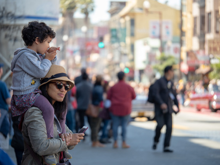 SAN FRANCISCO, CA – MAY 27, 2018: A mother and child enjoying the 40th annual Carnaval Grand Parade in San Francisco's Mission District