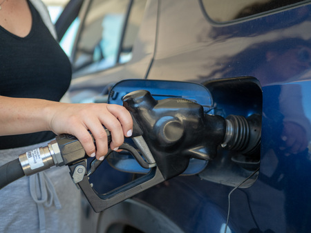 A woman pumping gas with a handheld fuel nozzle at a gas station Stock Photo