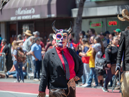 A woman wearing a devil mask and cracking a whip walks down the street at a parade