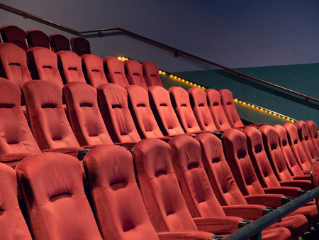 Some orange, art deco fuzzy movie theater seats in an empty theater