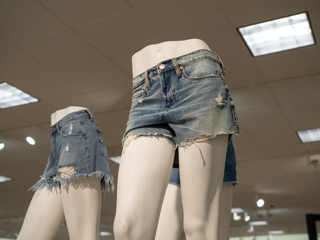 Some lower bodies of woman mannequins wearing jean shorts in a department store