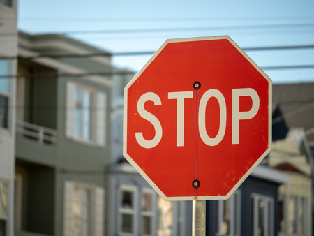 A stop sign in a residential neighborhood with copy space to the left on a sunny day