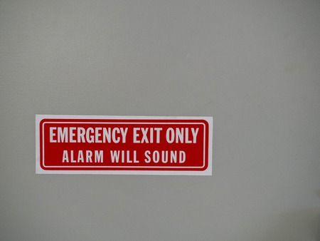 Emergency exit only, alarm will sound sign posted on a white door