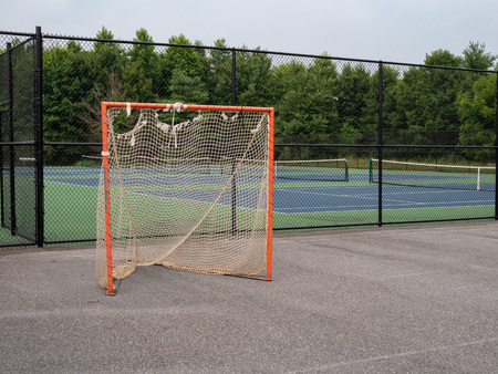 Offseason, beat up, rusted, ragged lacrosse goal sitting on asphalt court, nets tearing