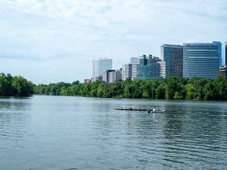 Rowers practice on the Potomac River with office buildings in Arlington, VA in background