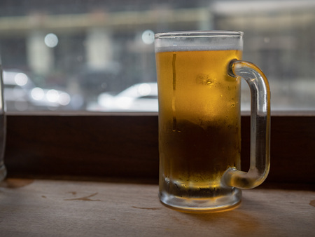 Large frosty beer mug filled with lager sitting on counter top