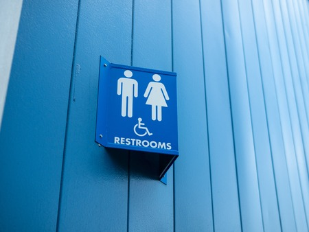 Men and woman handicap available sign outside of restroom