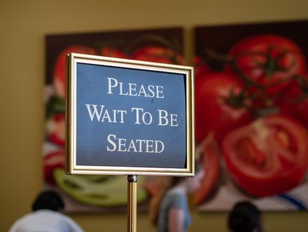 Veuillez attendre d'être assis signe debout à l'avant d'un restaurant
