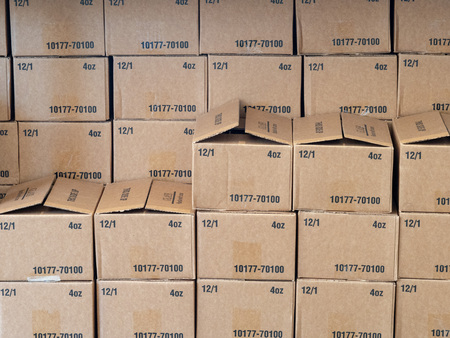 Rows and stacks of cardboard boxes sitting inside a warehouse