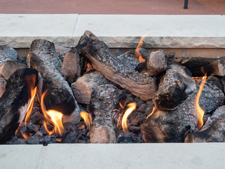 Logs sitting in open fire in a white stone firepit