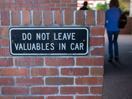 Some people walking away from do not leave valuables in car sign