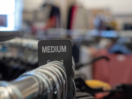 Medium section sign on steel clothing rack with hangers in department store 版權商用圖片