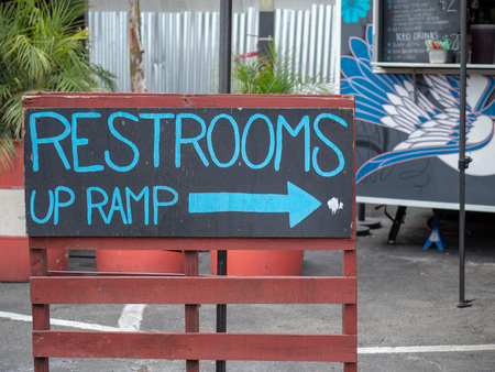 Blue handwritten restrooms up ramp sign on chalk board pointing  right Banco de Imagens