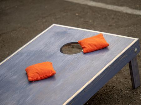 Orangefarbene Sitzsäcke sitzen auf einer blauen Cornhole-Board-Plattform