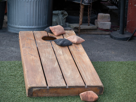 Sets of beanbags in competitive game of cornhole on a lumber platform 写真素材
