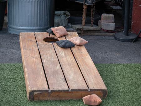 Sets von Sitzsäcken im kompetitiven Spiel von Cornhole auf einer Holzplattform Standard-Bild