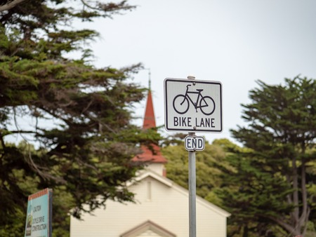 Bike lane end sign handing in front of a church outdoors