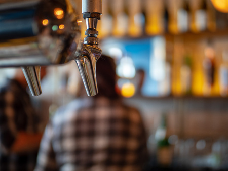 Silver beer tap in restaurant bar with hard drinks and liquor in background Stock Photo