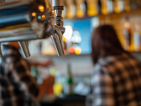 Silver beer tap in restaurant bar with two bartenders Stock Photo