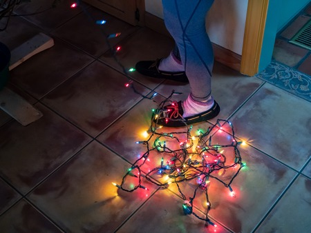 Tangled string of Christmas lights at the bottom at a womans feet while decorating a Xmas tree