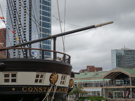 USS Constellation frigate war ship docked in Baltimore Inner Harbor with shopping in background