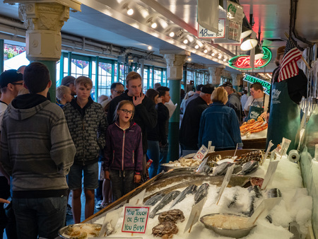 Young girl among crowd looking at fresh raw seafood at Pike Place Market