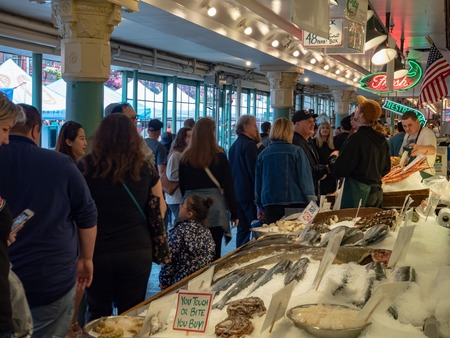 Crowd walking by raw seafood on ice at Pike Place Public Market
