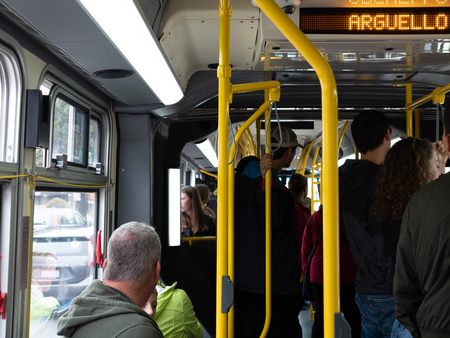Crowded standing room only bus on 38 Geary line on MUNI crossing Arguello St Editorial