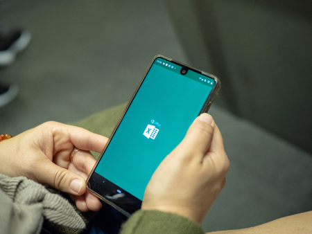 Woman opening Microsoft Office 365 Excel app with logo on Android screen while commuting on subway train