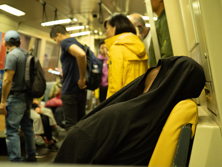 Man sleeps with shirt over his head on a crowded BART subway car