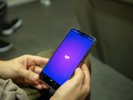 Woman opening Lyft mobile app with logo on Android screen while commuting on subway train