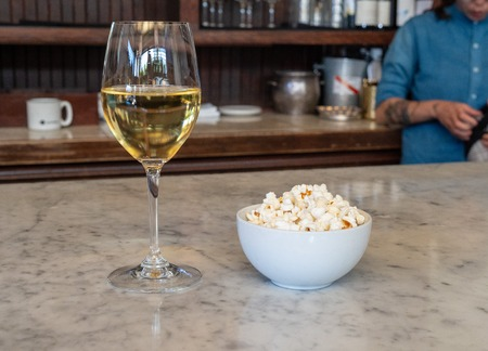 Wine glass filled with white wine standing next to a bowl of fresh popcorn with bartender Banco de Imagens
