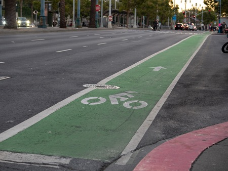 Green dedicated bike lane along city street in evening