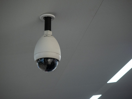 White circular surveillance camera on ceiling in a public setting attached to white ceiling Stock fotó